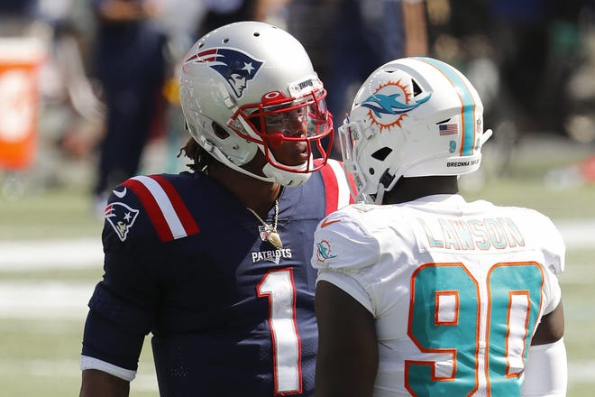 Patriots quarterback Cam Newton has words with Dolphins defensive end Shaq Lawson on Sunday.