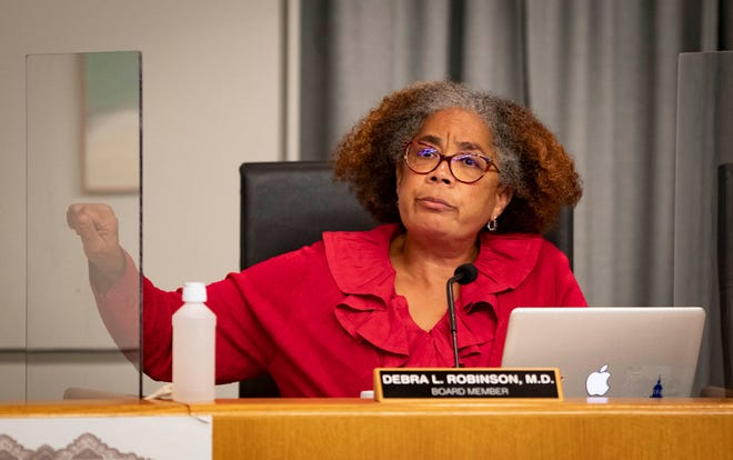 School board member Debra Robinson knocks on her plexiglass divider during a meeting at school district headquarters after hearing that some schools were still in need of dividers. [ALLEN EYESTONE/palmbeachpost.com]