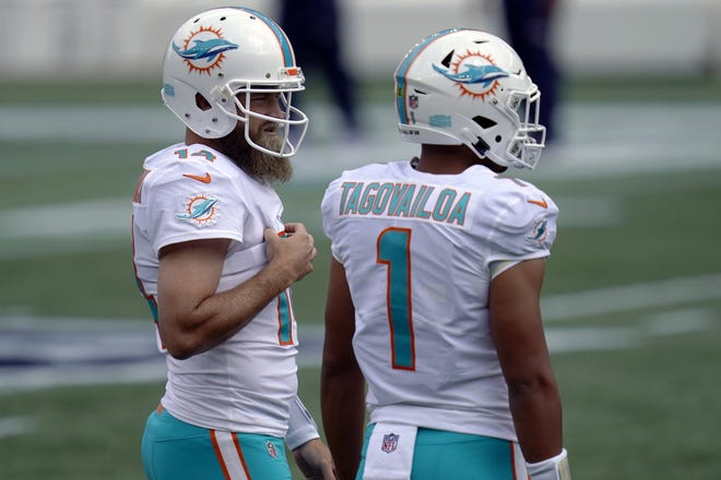 Miami Dolphins quarterbacks Ryan Fitzpatrick (14) and Tua Tagovailoa (1) warm up before an NFL football game against the New England Patriots, Sunday, Sept. 13, 2020, in Foxborough, Mass. (AP Photo/Charles Krupa)
