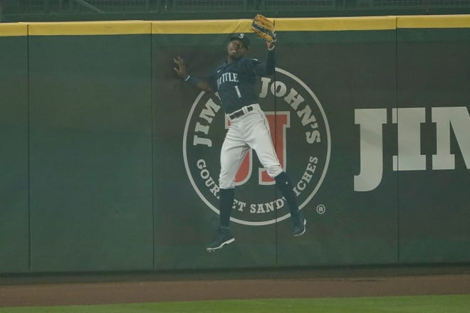 Seattle Mariners center fielder Kyle Lewis comes down after making a leaping catch of a deep fly ball hit by Oakland's Ramon Laureano with two outs and the bases loaded during the first inning of Monday's second game of a doubleheader in Seattle. The Mariners will play at San Francisco on Wednesday night.