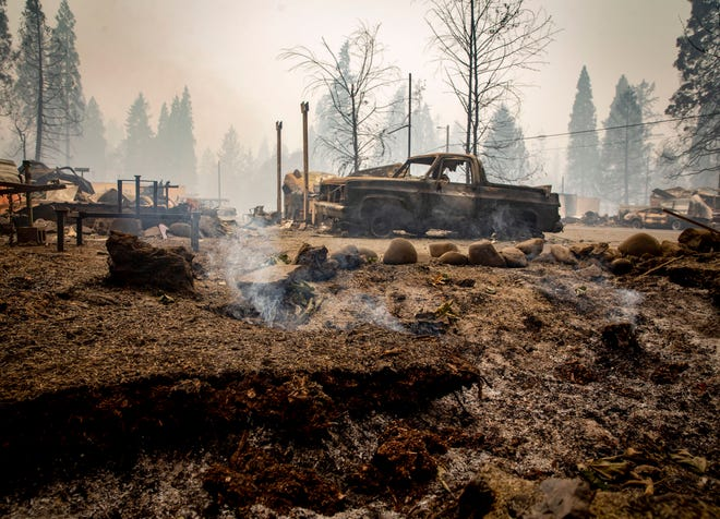 The ground still smokes in Blue River, Ore., Sept. 15, 2020, eight days after the Holiday Farm Fire swept through its business district. (pool photo by Andy Nelson/The Register-Guard)
