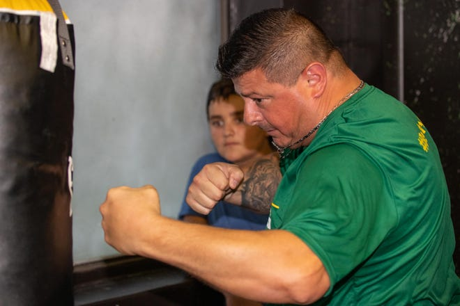 Nick Torchio, right, exhibits a jab-cross-hook combination to Nick Mendoza during a Sept. 15 open house at the Harris Community Center in Houston. Torchio will volunteer with the St. Johns Police Athletic League's boxing program.