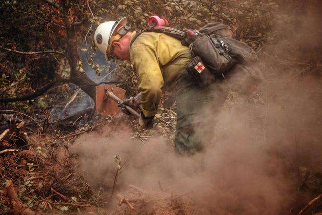 A firefighter works on Goodwish Creek Road in Oregon on the Slater Fire on Sept. 12, 2020.