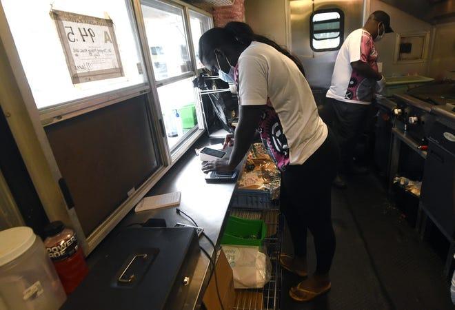 Sheniqua Scott takes an order at On Thyme food truck at the Stevenson Hendrick car dealership in Wilmington, N.C., Wednesday, September 16, 2020. Scott is the sister of owner Corey Scott.