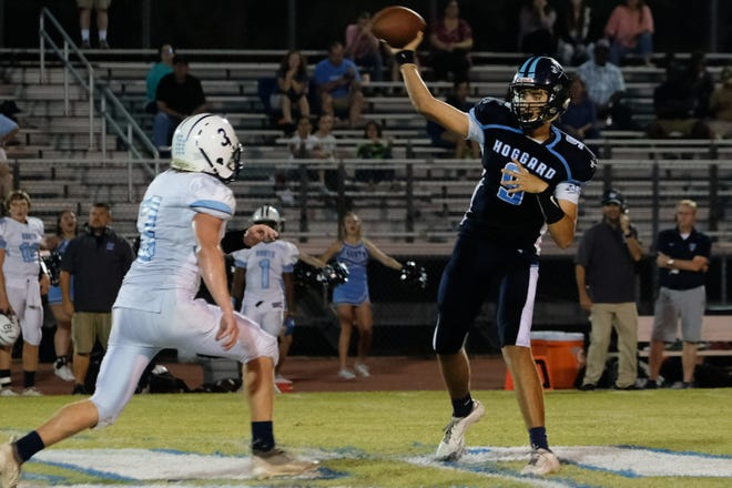 Hoggard's Gabe Johnson fires a pass before the oncoming rush of South Brunswick's Danny Parker in a Hoggard win last year. [KEN OOTS/FOR STARNEWS]