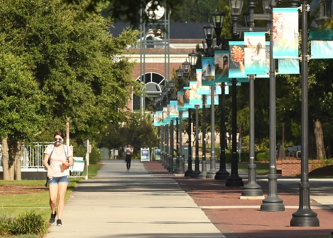 Some students a faculty walk across campus with and without masks Friday Sept. 11, 2020 at UNCW in Wilmington, N.C. while the coronavirus pandemic continues. The University was over the suggested capacity for their dorms and some outbreaks  have happened over the past few weeks.