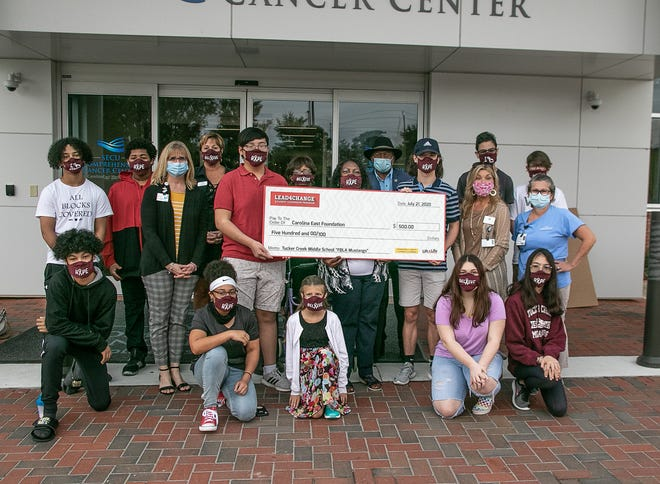 The Tucker Creek Middle School FBLA Mustangs awarded a $500 check to CarolinaEast Foundation's Journey of Hope, a support organization for cancer patients and their families. [Bill Hand / Sun Journal Staff]