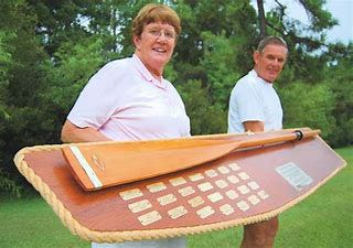 Olwen and Bill Jarvis carry the permanent John Walsh Memorial Oar Race trophy on which winners' names are inscribed each year. It hangs in the Fairfield Harbour Community Center during the year. [CONTRIBUTED PHOTO]