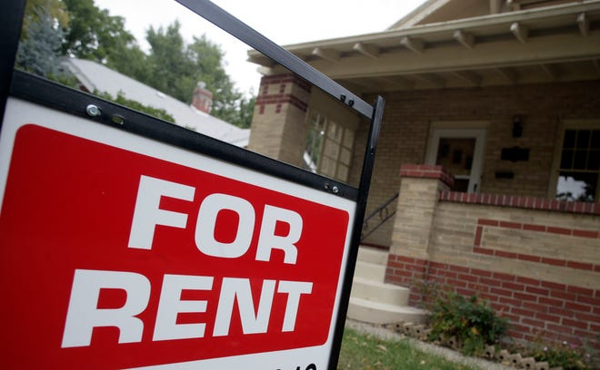 "A ""For Rent"" sign stands outside a home."