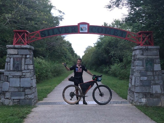 Brent Tucker, a member of the West Alabama Mountain Biking Association, celebrates at the finish line at Silver Comet Trail near the Alabama-Georgia line after riding 357 miles in the 2020 Trans North Georgia Adventure.