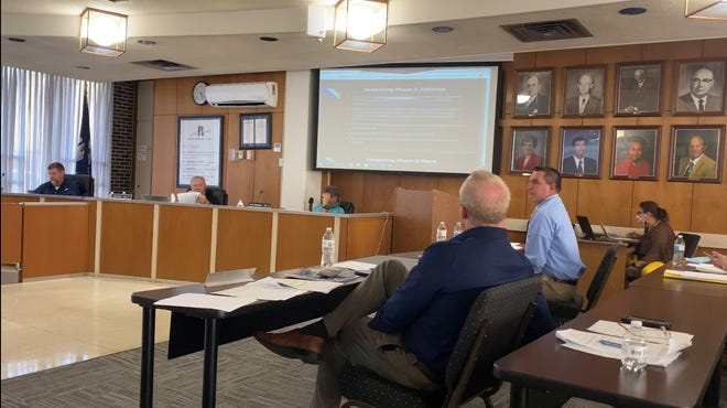 Rapides Parish Schools Superintendent Jeff Powell (right) briefs board members on a proposal to reimburse schools for hiring officials and security at upcoming football games. The motion was sent to the full board to consider at its October meeting.
