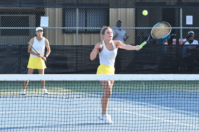 Abilene High's Kaitlyn Strain hits a shot at the net in front of No. 1 girls doubles partner Ruth Hill during the fall team tennis season at the AHS Tennis Courts.