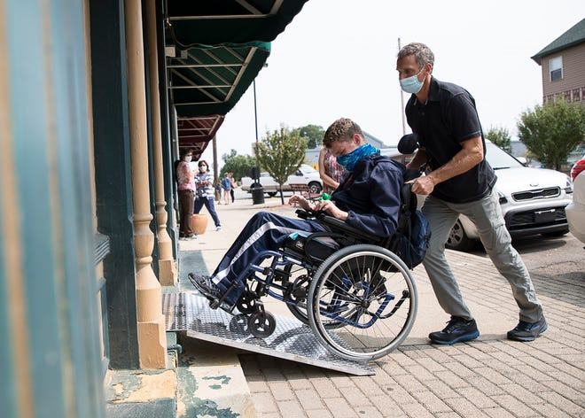 Paul Lincke, right, and AJ Hawk, a Chillicothe High School student, try out one of the new portable wheelchair ramps made possible by a fund through the Foundation of Appalachia received by Downtown Chillicothe and First Capital Enterprises.