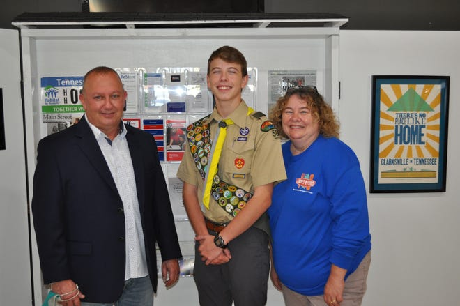 HFHMCTN Executive Director Rob Selkow, Eagle Scout Taydan Jackson, and Loaves & Fishes Executive Director Rita Burnett stand in front of the Community Kiosk.