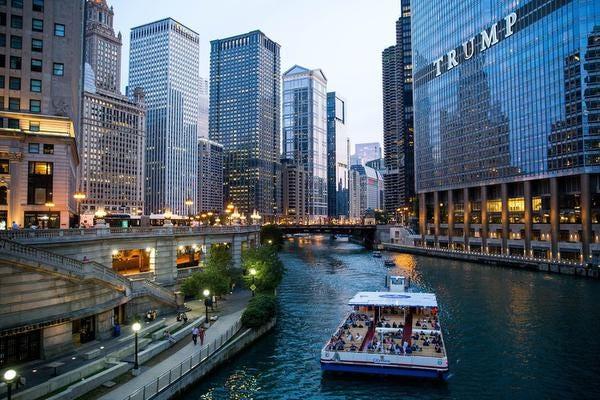 Sebuah perahu Tamasya Shoreline mengapung di sepanjang Sungai Chicago selama tur perahu arsitektur di Chicago.