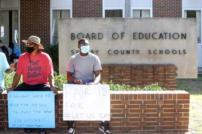 George Thomas Jr. and his son George III join fellow parents and student athletes gathered outside the Shelby County Board of Education offices to protest the decision to postpone fall sports in the district on Wednesday, Sept. 16, 2020.