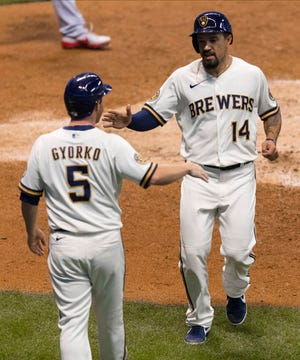 Jace Peterson is greeted by Jeff Gyorko after they both scored on a single by Omar Narvaez against the Cardinals.