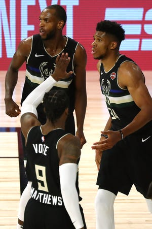 Sep 2, 2020; Lake Buena Vista, Florida, USA; Milwaukee Bucks forward Giannis Antetokounmpo (34) reacts with guard Wesley Matthews (9) and forward Khris Middleton (22) after being fouled against the Miami Heat during the second half of game two of the second round of the 2020 Stanley Cup Playoffs at The Field House. Mandatory Credit: Kim Klement-USA TODAY Sports