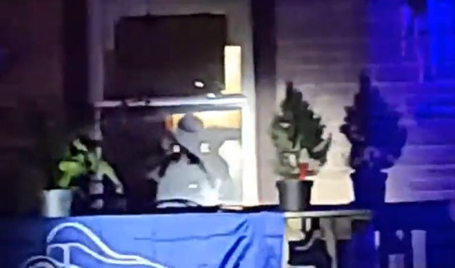A silhouetted figure in a house on the 3400 block of West 80th Street in Milwaukee appears to be holding a shotgun as protesters shine a light on the home Tuesday evening. Protesters on social media said they were demonstrating against the man for using racial slurs against neighbors. The man was arrested by police for allegedly pointing the weapon at the crowd.