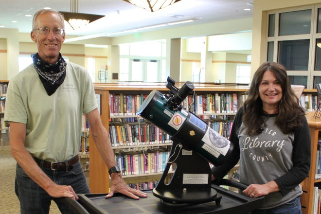 Jeffrey Hoeper, Baxter County Library volunteer and Arkansas Master Naturalist, delivers telescopes to Library Director Kim Crow Sheaner.