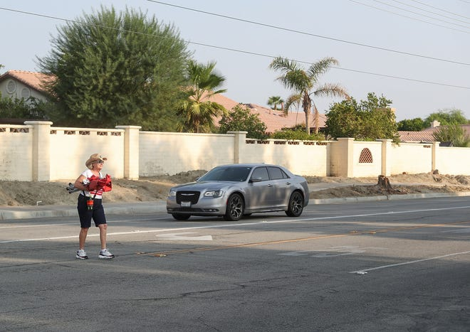 Leslie Hartzell of La Quinta crosses Adams Street at La Palma Drive where local residents would like a crosswalk installed there where Adams Park is, September 15, 2020. The city of La Quinta is planning to reduce the number of traffic lanes on Adams, between Miles Avenue and Fred Waring Drive, from four to two in an effort to slow speeding motorists and make the roadway safer for pedestrians want to use the park.