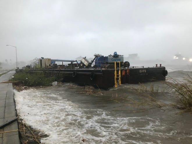 A Skanska company barge ran aground along Bayfront Parkway in downtown Pensacola on Wednesday as Hurricane Sally moved inland.