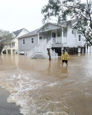 Blake Hess wades through flood water outside his damaged home along Scenic Highway as Hurricane Sally moves through Pensacola, Florida, Wednesday, Sept. 16, 2020.