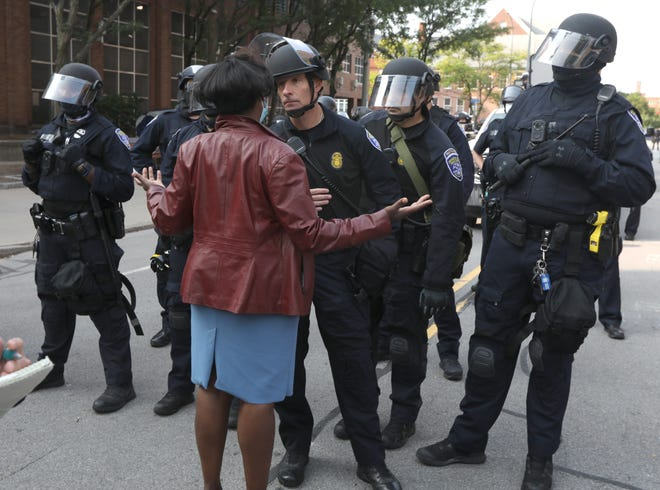 The Rev. Myra Brown, Spiritus Christi Church, talks to Rochester Police, looking for a more peaceful resolution as the police clear Black Lives Matter protesters from their encampment surrounding City Hall Wednesday morning, Sept. 16, 2020.