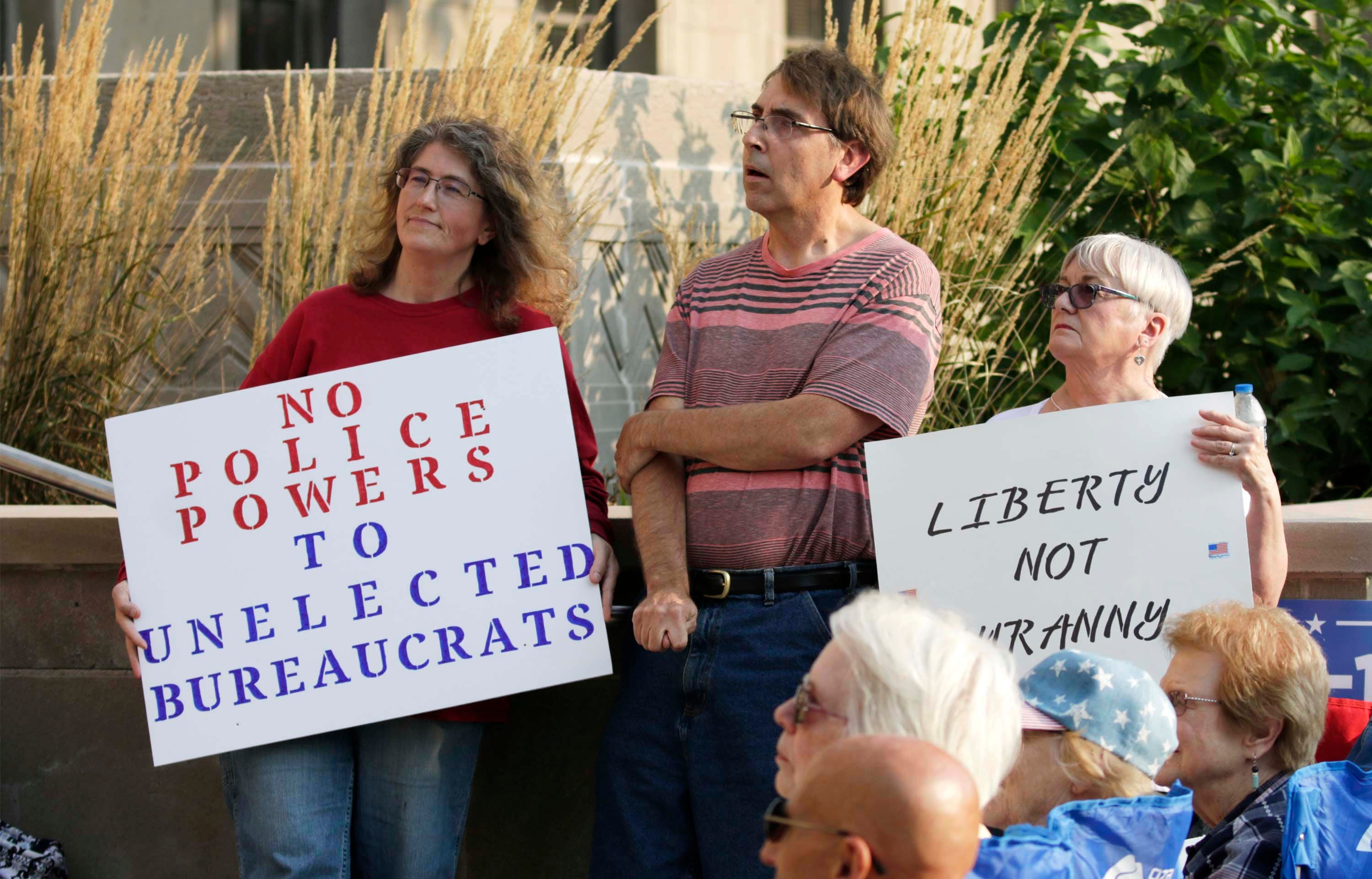 People hold signs at the Freedom Rally in front of the Sheboygan County Courthouse, Tuesday, September 15, 2020, in Sheboygan, Wis. The group urged the county board to file ordinance number 3 which would, according to the group, give unelected bureaucrats excessive power.