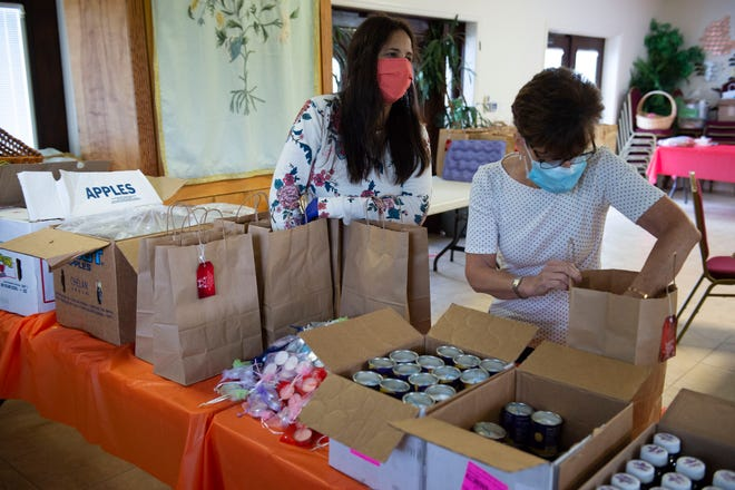 """Daniella Uminer (left), wife of Chabad Jewish Center of Martin and St. Lucie County Rabbi Shlomo Uminer, and volunteer Diane Fried, of Port St. Lucie, pack High Holy Days celebration kits filled with apples, honey, grape juice, candles, challah bread and a book of prayers on Wednesday, Sept. 16, 2020, in Palm City. The team is creating about 300 kits to be distributed to members and assisted living facilities. """"Even if they're home, they're not disconnected, they have what they need, they can celebrate,"""" said Rabbi Uminer."""