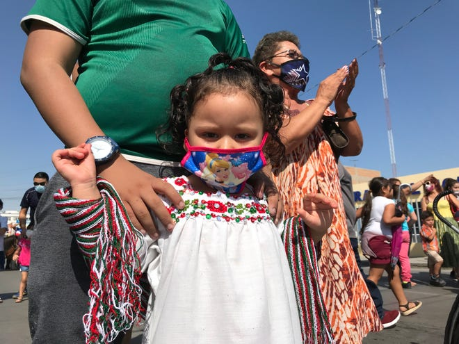 The Nuñez family turned out for a scaled-back parade in Juárez celebrating Mexico's Independence Day on Sept. 16, 2020. Pictured is 3-year-old Arianna, who was wearing a face mask for protection against the coronavirus.
