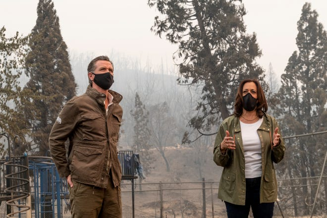 Vice-president candidate Kamala D. Harris, right, and California Governor Gavin Newsom talk to the media at Pine Ridge School in Auberry, CA on Tuesday, Sept. 15, 2020. The area in the background was damaged by the Creek Fire.