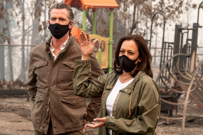 Vice-president candidate Kamala D. Harris, right, and California Governor Gavin Newsom talk to the media at Pine Ridge School in Auberry, CA on Tuesday, Sept. 15, 2020. The playground set in the background was damaged by the Creek Fire.