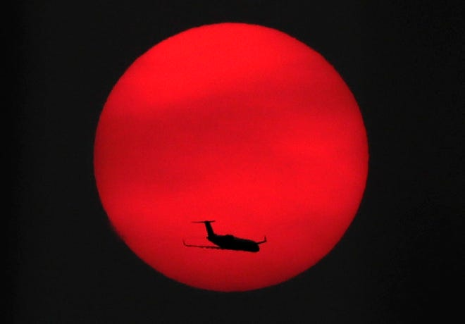 An airplane crosses in front the setting sun on Tuesday, September 15, 2020, near Appleton, Wis. The sun is seen through the filter of skies made hazy by smoke from forest fires on the West Coast