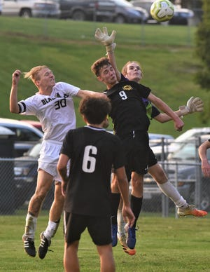 Tri-Valley keeper Carson Hennessy tries to swat the ball away while teammate Jack Hehr (9) and River View's Jordan Bryant try to head it in Tuesday's match at Kenny Wolford Park. Tri-Valley won 2-1.