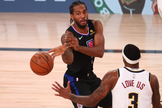 Clippers forward Kawhi Leonard passes the ball while Denver Nuggets forward Torrey Craig defends during the second half in Game 7 at ESPN Wide World of Sports Complex.