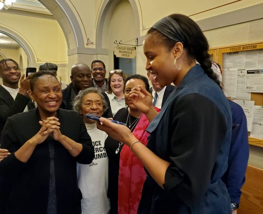 Ex-WNBA star Maya Moore, right, calls Jonathan Irons as supporters react in Jefferson City after Cole County Judge Dan Green overturned Irons' convictions in a 1997 burglary and assault case. Moore is now married to Irons.