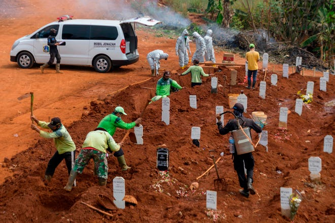 """Workers dig holes at a burial site for victims of COVID-19 in Jakarta, Indonesia, on September 11, 2020. Indonesia's capital planned to reimpose a partial lockdown as early as Sept. 14 over fears that surging coronavirus cases could """"collapse"""" its under-pressure hospitals, the city's governor said."""