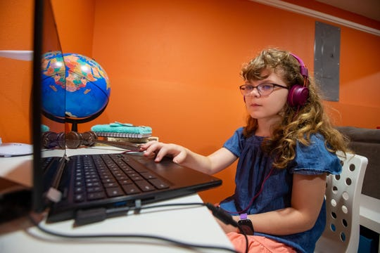 Alice DeWaard, a fifth grade student at Mitchell Elementary School, takes part in an online class at her home in Ames, Iowa on Sept. 14, 2020.