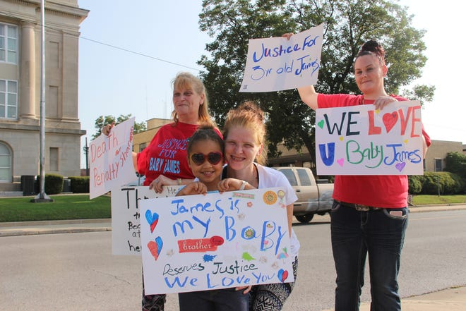 Kyla Burgess, her seven-year-old daughter, Karmen, and family hold up signs outside of the Carter County Courthouse on Sept. 17. Burgess lost her three-year-old son, James, last month and the child's aunt, Shannon Smith, is being investigated for his murder.