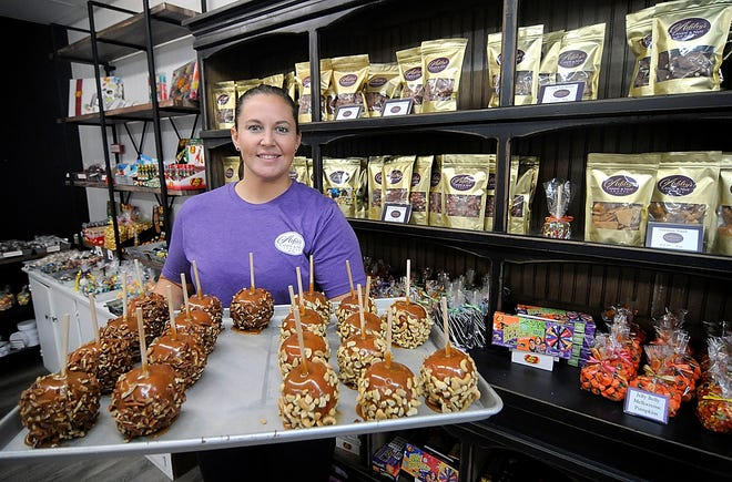 Ashley Kline poses with a freshly made tray of carmel apples in her store the Ashley's Candy & Nut Shoppe, 39 E. Main Street in Ashland, on Thursday, Sept. 17, 2020. Tom E. Puskar, Times-Gazette.com