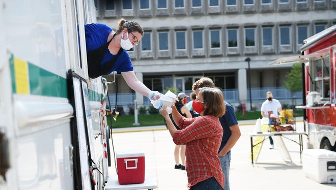 Melissa Haynes of Finley Curbside Beasrea serves foods to customer Adriana Lisman from the food truck at Osborn Drive at Iowa State University on Thursday, Sep. 17, 2020, in Ames, Iowa.