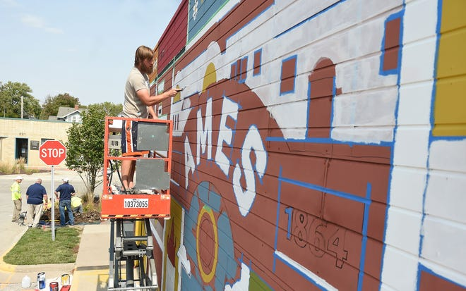 Artist Andrew Maahs works on a mural on Main Street in downtown Ames, Wednesday, Sept. 16, 2020, in Ames, Iowa.