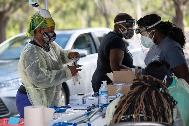Health care workers process a test for COVID-19 at Lake-Sumter State College in Leesburg. [Cindy Peterson/Correspondent]