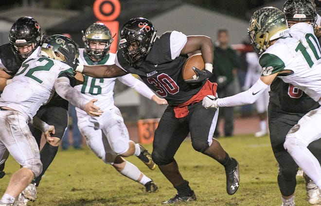 In this photo from last year's Class 4A-Region 2 semifinals at Inman Sherman Field in Bushnell, South Sumter's Malachi Presley (30) powers through defenders from The Villages. [PAUL RYAN / CORRESPONDENT]