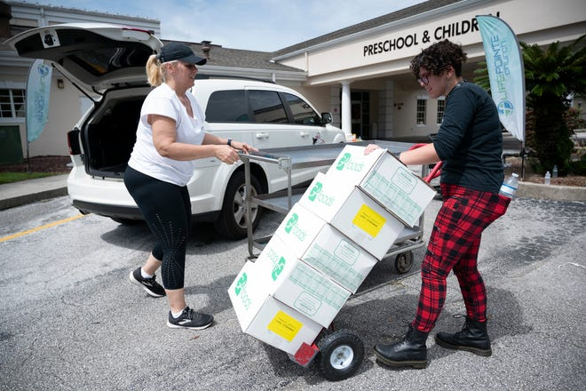 Volunteers from the group One To Another load food boxes into cars to be distributed throughout Lake and Sumter County on Wednesday. [Cindy Peterson/Correspondent]
