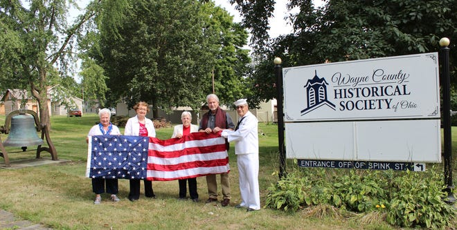 The Wayne County Historical Society received a new flag to fly over its Bowman Street campus from Emblem Club 374 of Wooster. Making the presentation to historical society President Doug Jones were (l. to r.) Emblem Club members Paulette Douglas, Ardenna Hurt, and Vera Rouhier, assisted by Larry Drabenstott of the 555th Honors Detachment