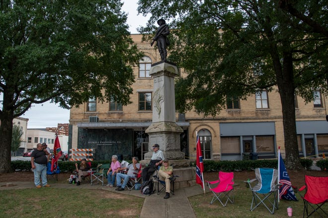 As the sun begins to set a group gathers in front of the Confederate Monument across from the Old Davidson County Courthouse on Main Street in Lexington. [Scott Pelkey / The Dispatch][Scott Pelkey / The Dispatch]