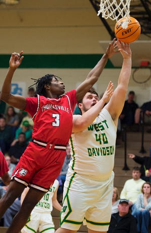Thomasville's Malcolm Knight (3) defends as West Davidson's Harrison Gobble takes a shot during a game in the 2019-20 season.
