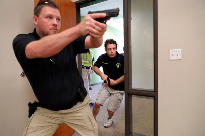 In this July 21, 2019 file photo, trainees Chris Graves, left, and Bryan Hetherington, right, participate in a security training session at Fellowship of the Parks campus in Haslet, Texas. An industry has sprung up following mass shootings at houses of worship around the country to train civilians to protect their churches with the techniques and equipment of law enforcement.
